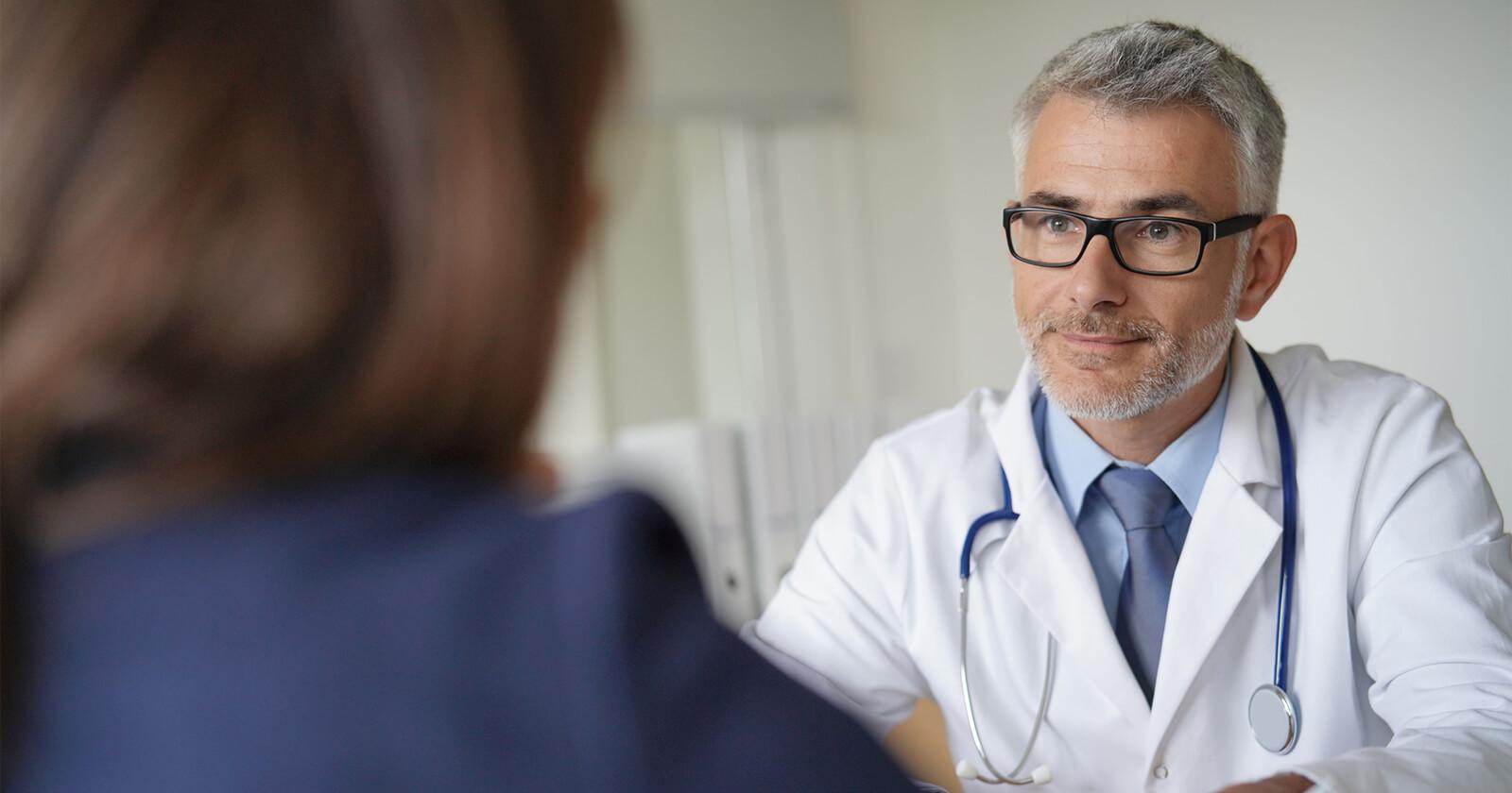 Arzt stellt Patientin Möglichkeiten zur Hämorrhoiden-Therapie vor, unter anderem die Posterian® akut Salbe.