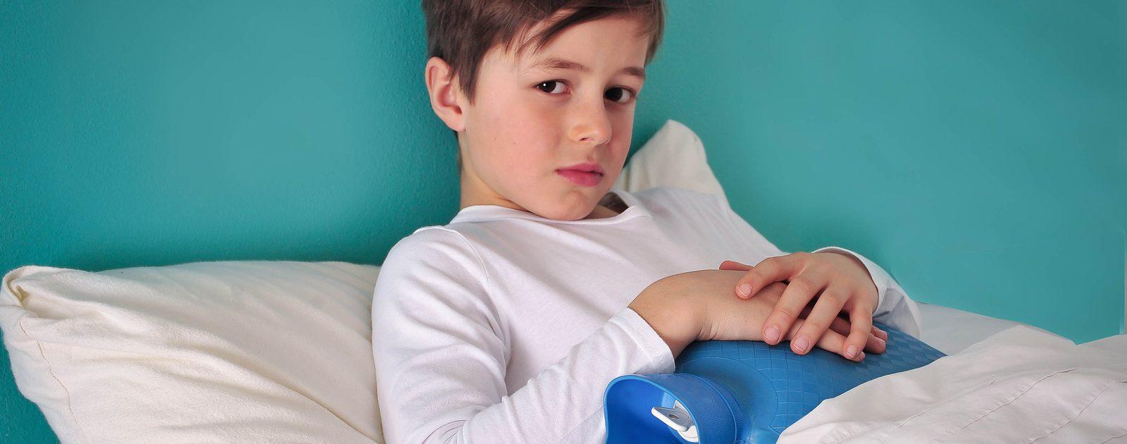 Junge mit Darmkrämpfen liegt mit Wärmflasche im Bett