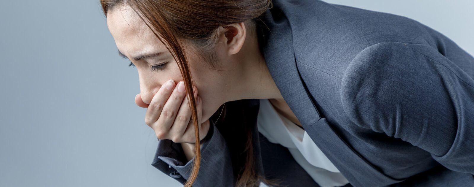 Eine Frau hat sich den Magen verdorben und hält sich die Hand vor den Mund, um sich nicht zu übergeben.