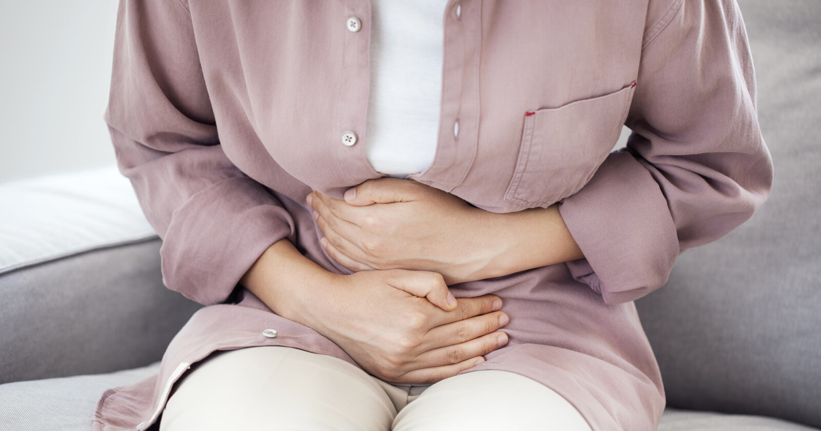 Eine Frau mit Magengeschwür hält sich den schmerzenden Bauch