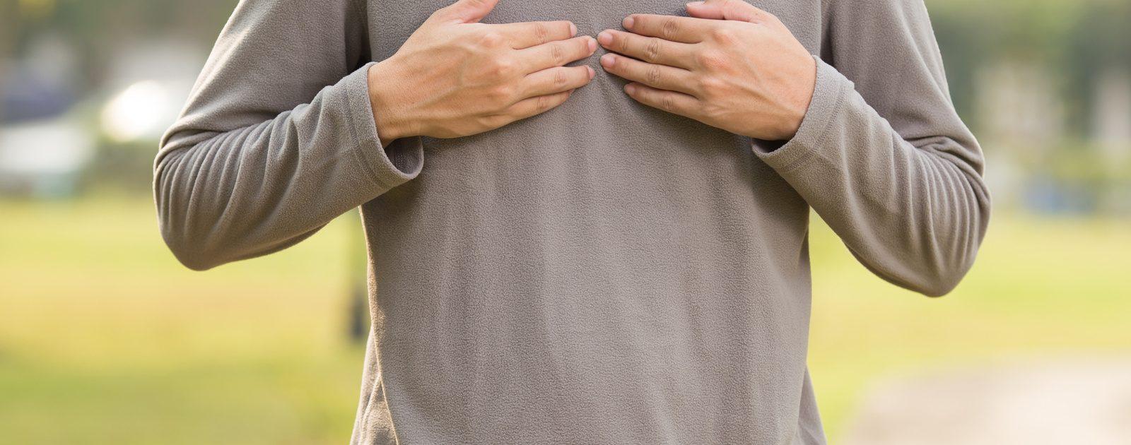 Mann fasst sich an die Brust