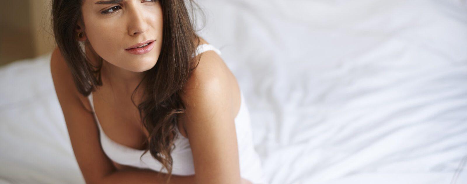 Frau sitzt im Bett und hält sich den Bauch