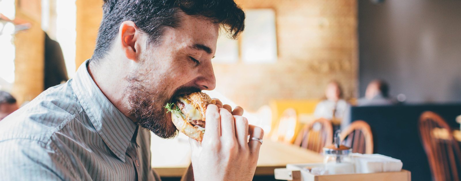 Mann isst fettiges Essen, welches Motilitätsstörungen verursachen kann