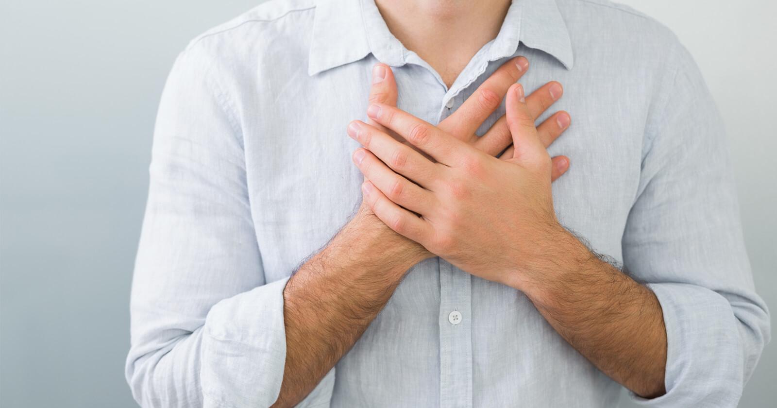 Ein Mann greift sich an die Brust, weil er sauer aufstoßen muss. Rennie® lindert die Beschwerden.