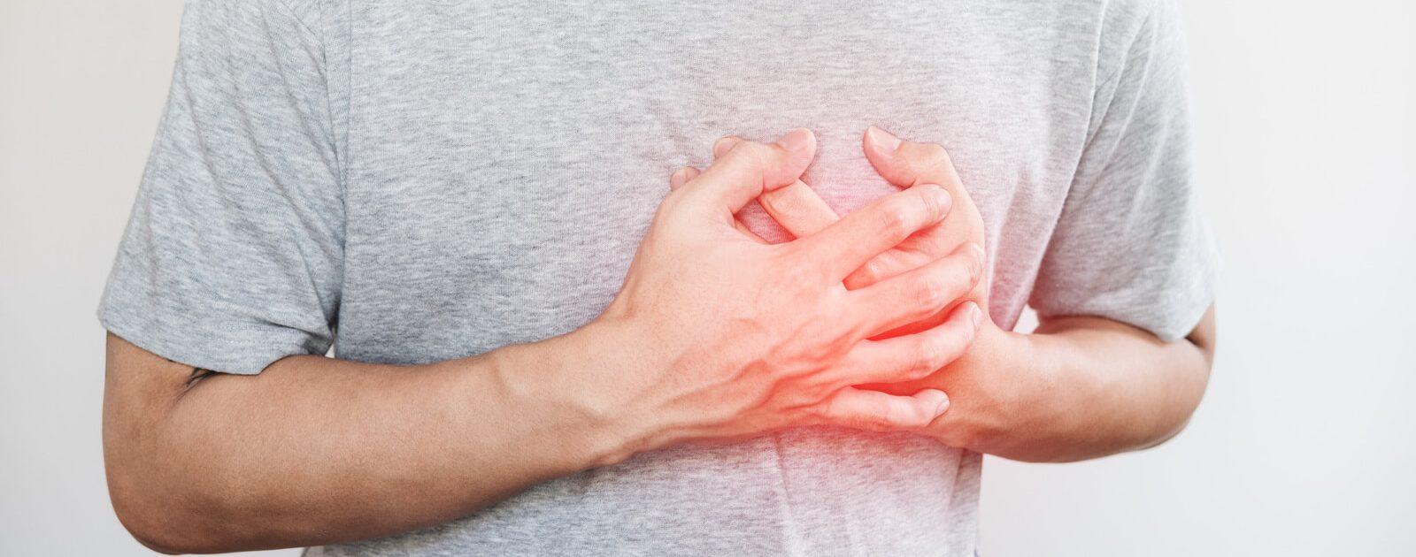 Mann, der am Roemheld-Syndrom leidet, hält sich die Brust aufgrund von Herzinfarkt-ähnlichen Schmerzen