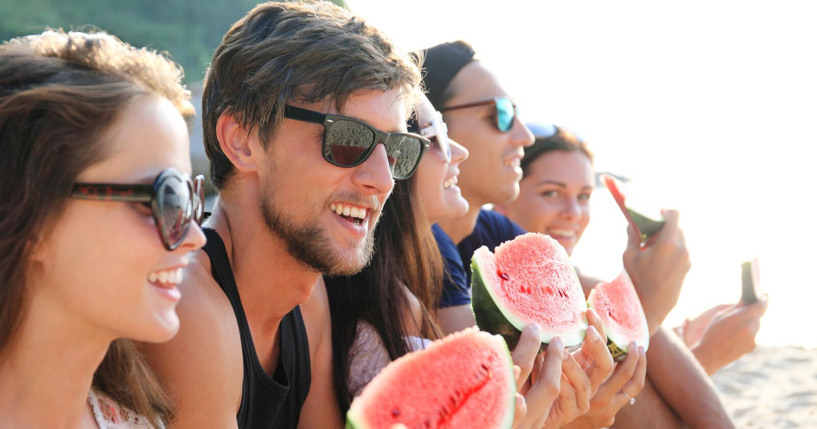 Gruppe von Freunden genießt am Strand eine Melone: Dank Talcid® Kautabletten müssen sie keine Angst vor Sodbrennen und Co. haben.