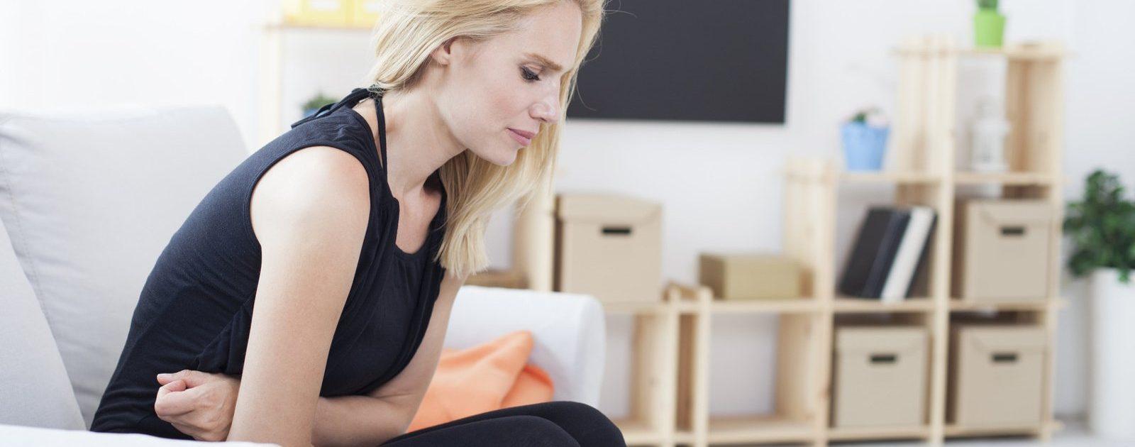 Frau hält sich den schmerzenden Bauch: Bei langanhaltenden, starken Bauchschmerzen sollte ein Arzt aufgesucht werden