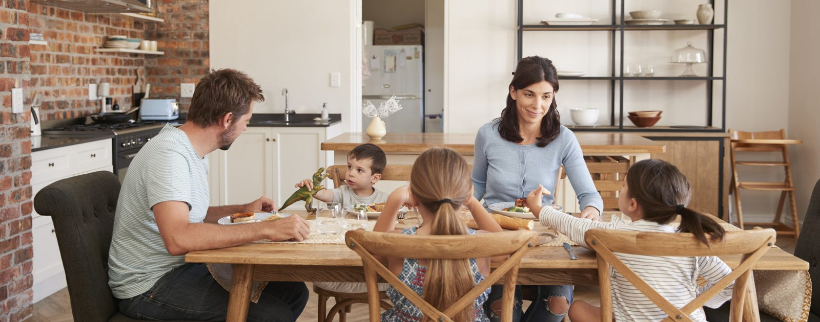Familie beim Essen. Der Darm ist wichtig für die Verdauung, allerdings reagiert er empfindlich auf Stress oder falsche Ernährung