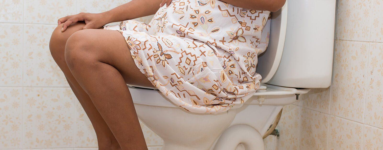 Schwangere Frau sitzt aufgrund von Durchfall auf der Toilette.