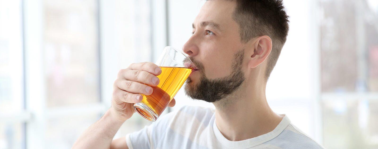 Mann trinkt für einen C13-Atemtest beim Arzt ein Glas Saft.