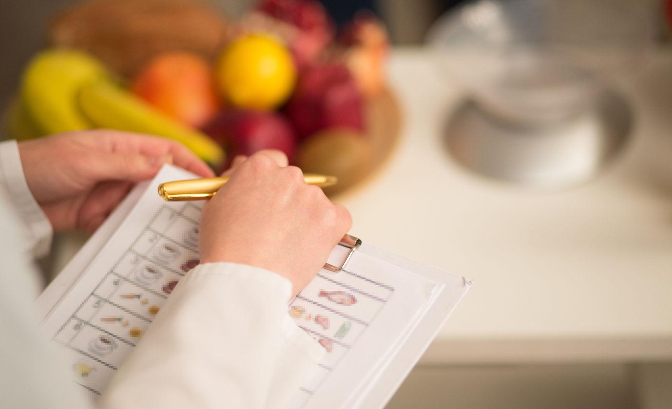 Colitis ulcerosa-Patientin führt ein Ernährungstagebuch, um herauszufinden, welche Lebensmittel sie schlecht verträgt.