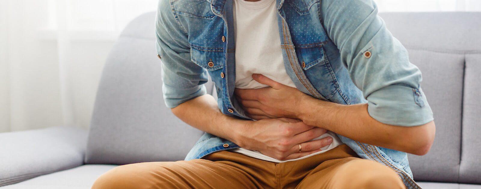 Mann leidet unter ständiger Übelkeit und hält sich den Bauch.
