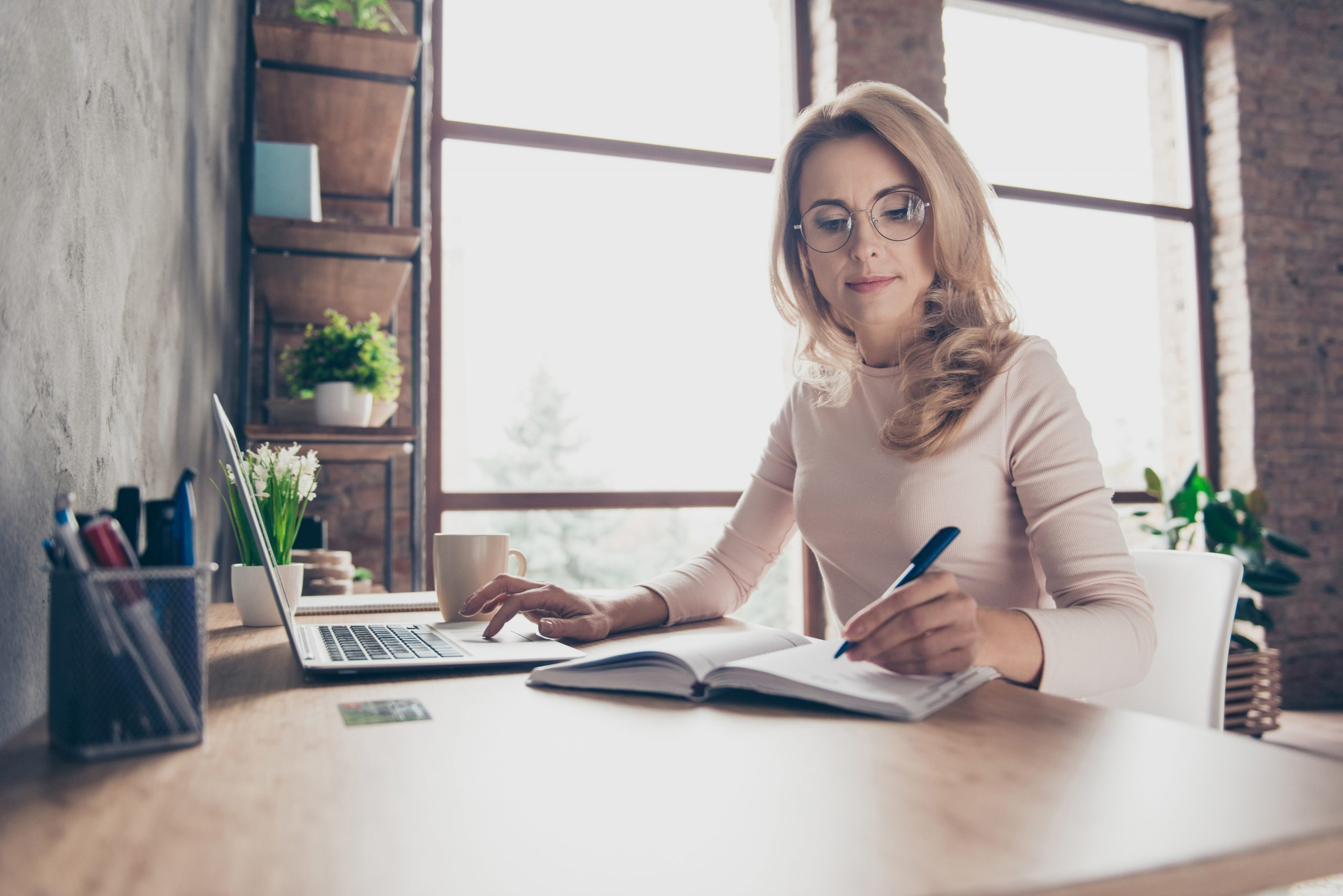 Businessfrau, die dank Iberogast® Advance ein besseres Wohlbefinden hat und nicht länger an Magen-Darm-Beschwerden leidet, arbeitet an ihrem Schreibtisch.