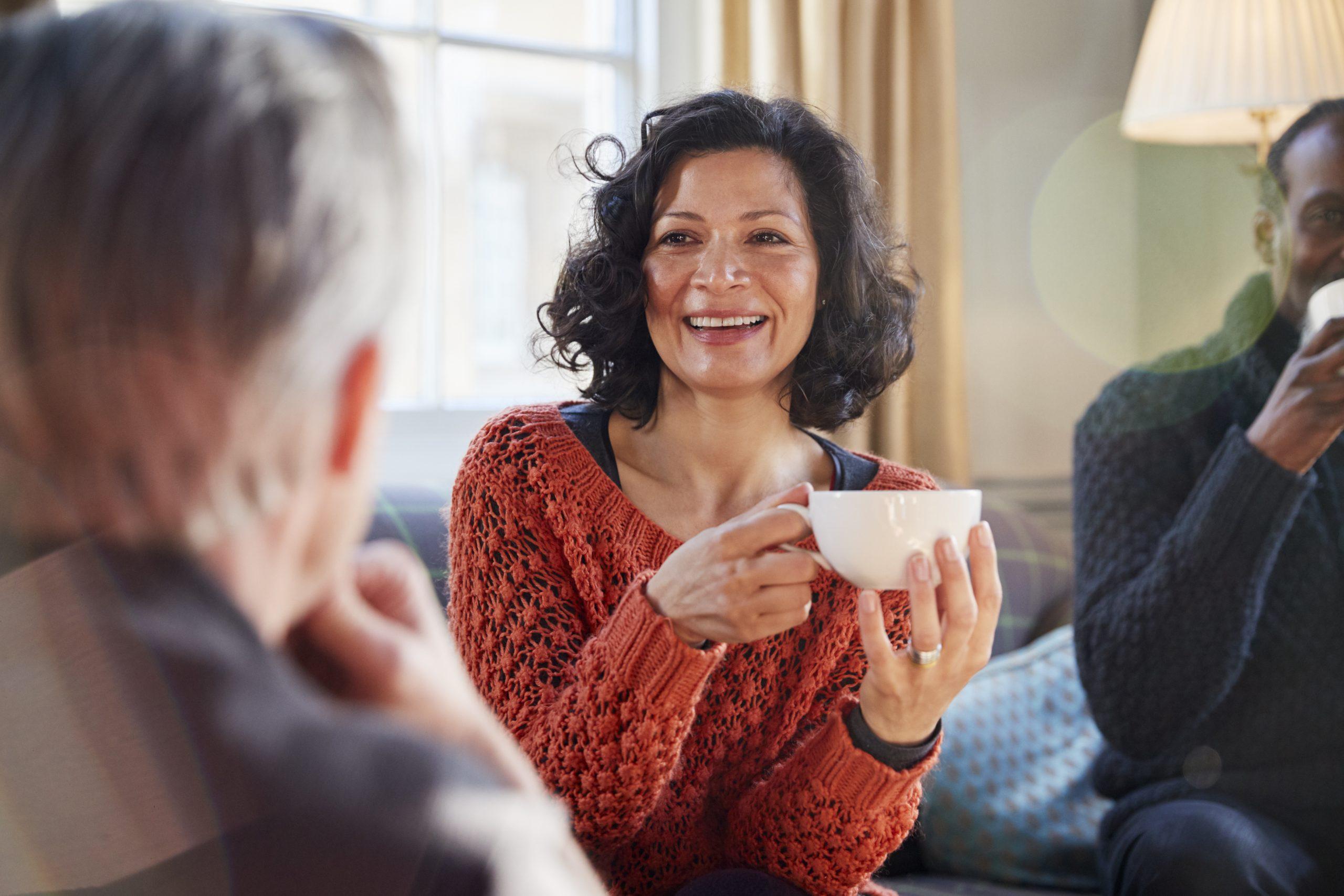 Frau mittleren Alters genießt einen Tee mit Freunden und freut sich, dass sie dank Iberogast® Advance keine Magen-Darm-Beschwerden hat.
