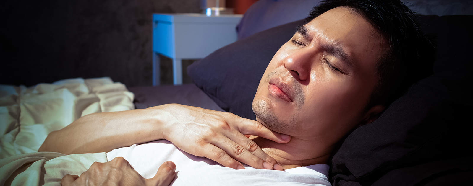 Mann liegt im Bett und hält die Hand an den Hals – er leidet unter nächtlichem Sodbrennen.