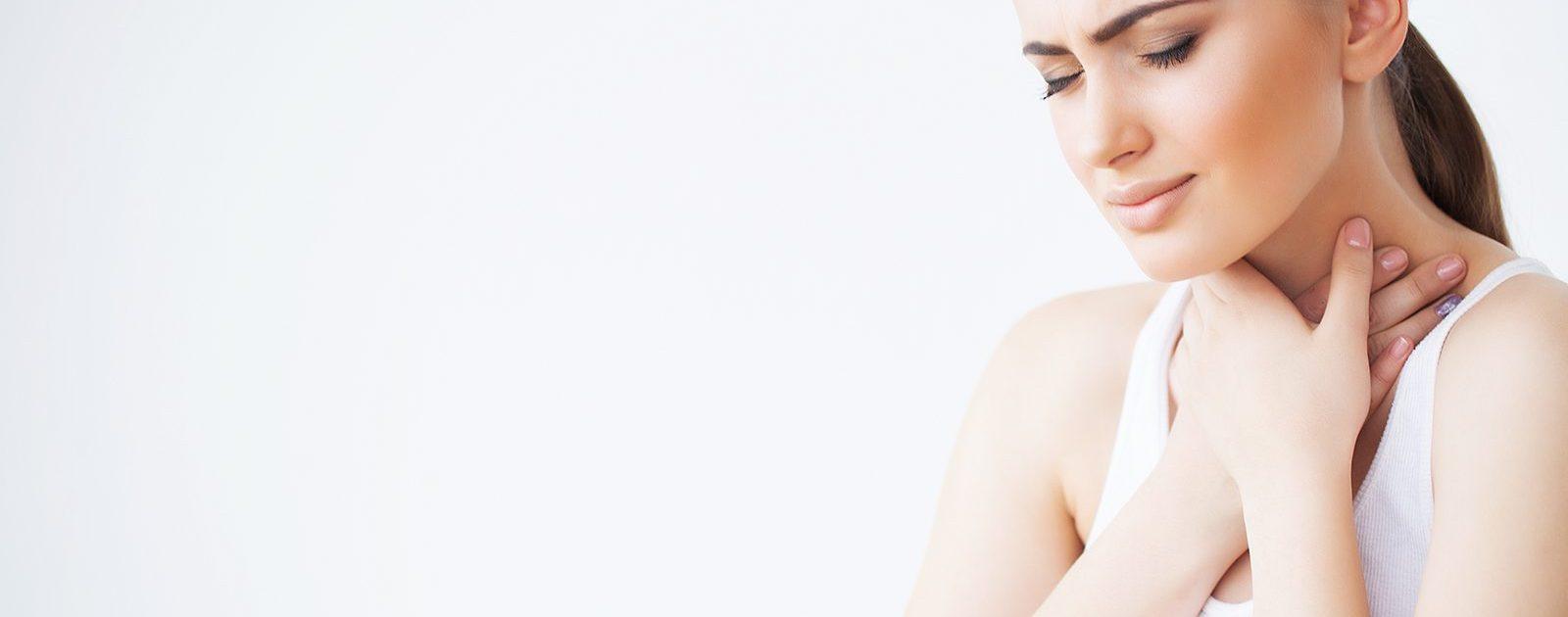 Frau mit Achalasie hält sich Hand an den Hals, da sie Schluckbeschwerden hat – ein typisches Symptom der Erkrankung.
